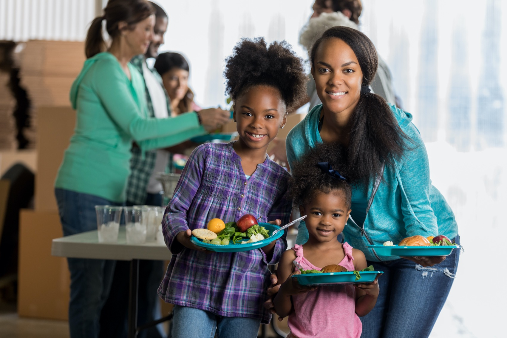 Beautiful young African American mom and her elementary and preschool age daughters hold plates of healthy food from a soup kitchen. Volunteers are serving in the background.
